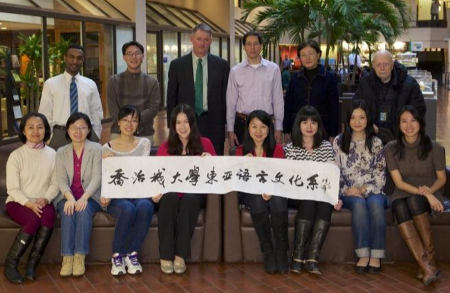 Department of East Asian Languages & Cultures faculty, staff, and visiting researchers holding a banner.