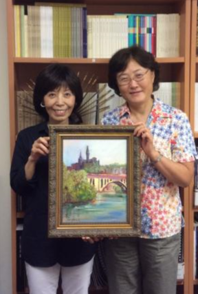 Professor Yu with a colleague holding up a painting of Georgetown University.