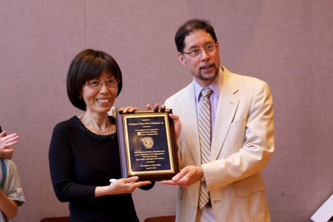 Professor Yu holding a plaque.
