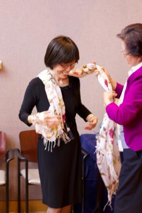 Professor Yu being handed a scarf.